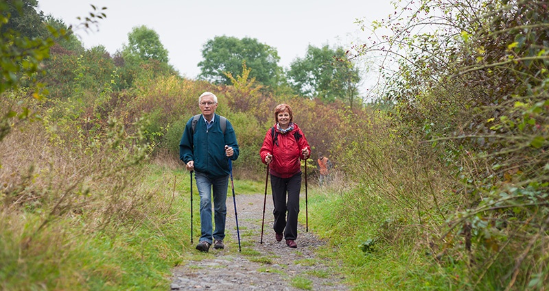 senior couple walking on a trail
